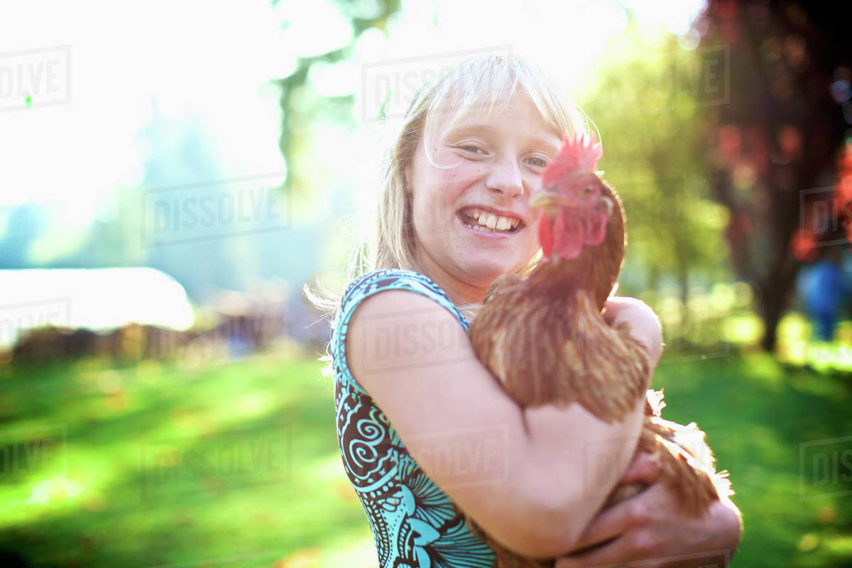 Portrait happy girl holding hen in sunny yard Royalty-free stock photo