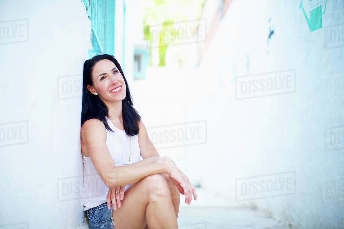 Portrait smiling, confident woman relaxing in summer alley Royalty-free stock photo