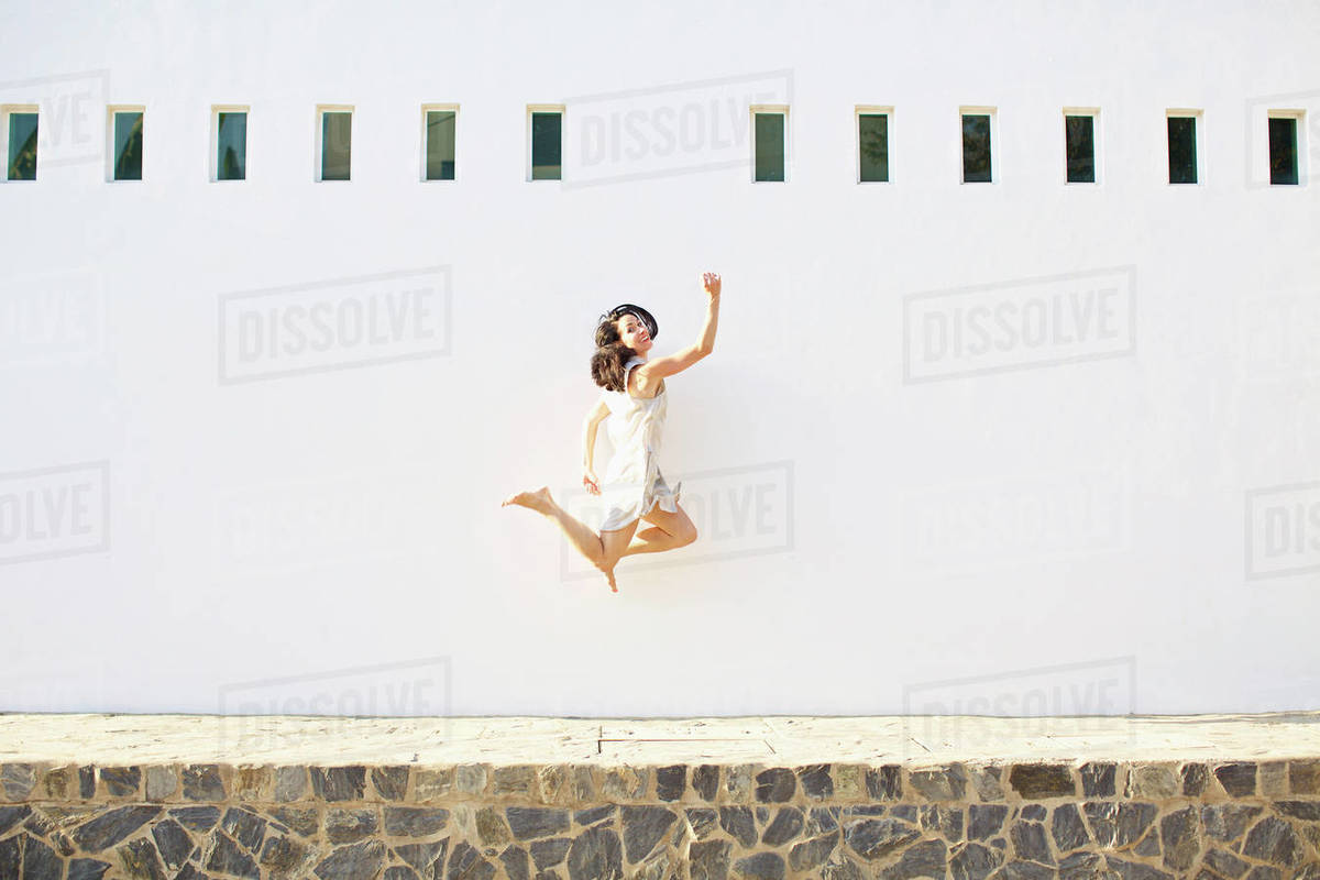 Portrait happy, carefree woman jumping for joy against sunny summer wall Royalty-free stock photo