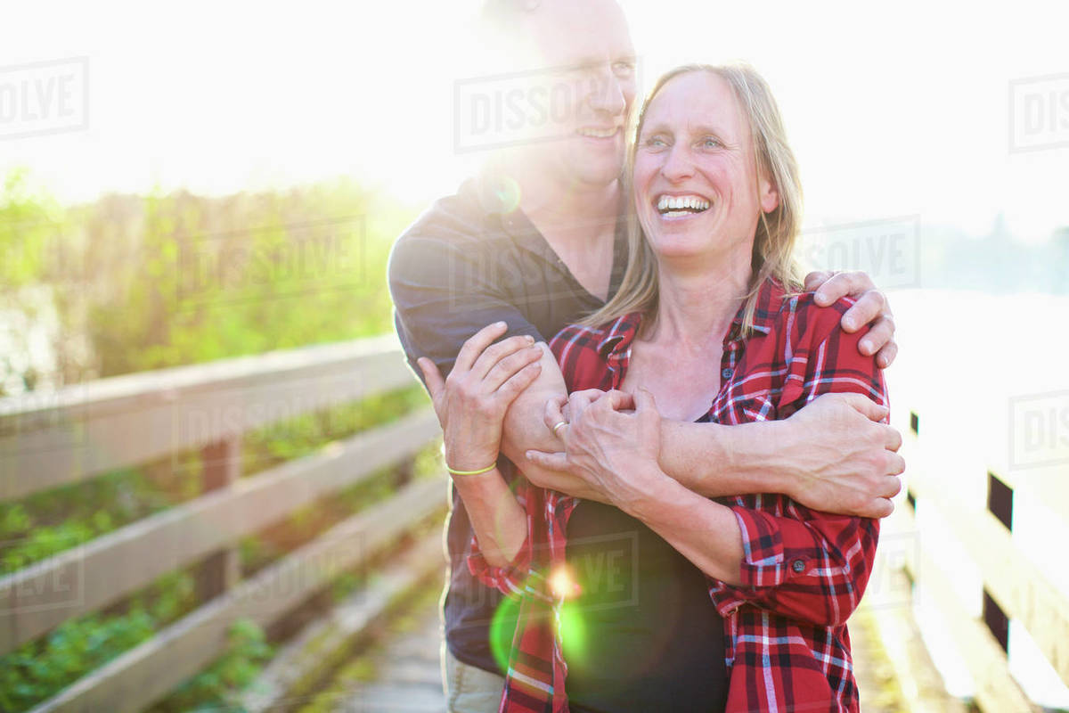 Portrait happy, affectionate couple hugging on sunny summer footbridge Royalty-free stock photo