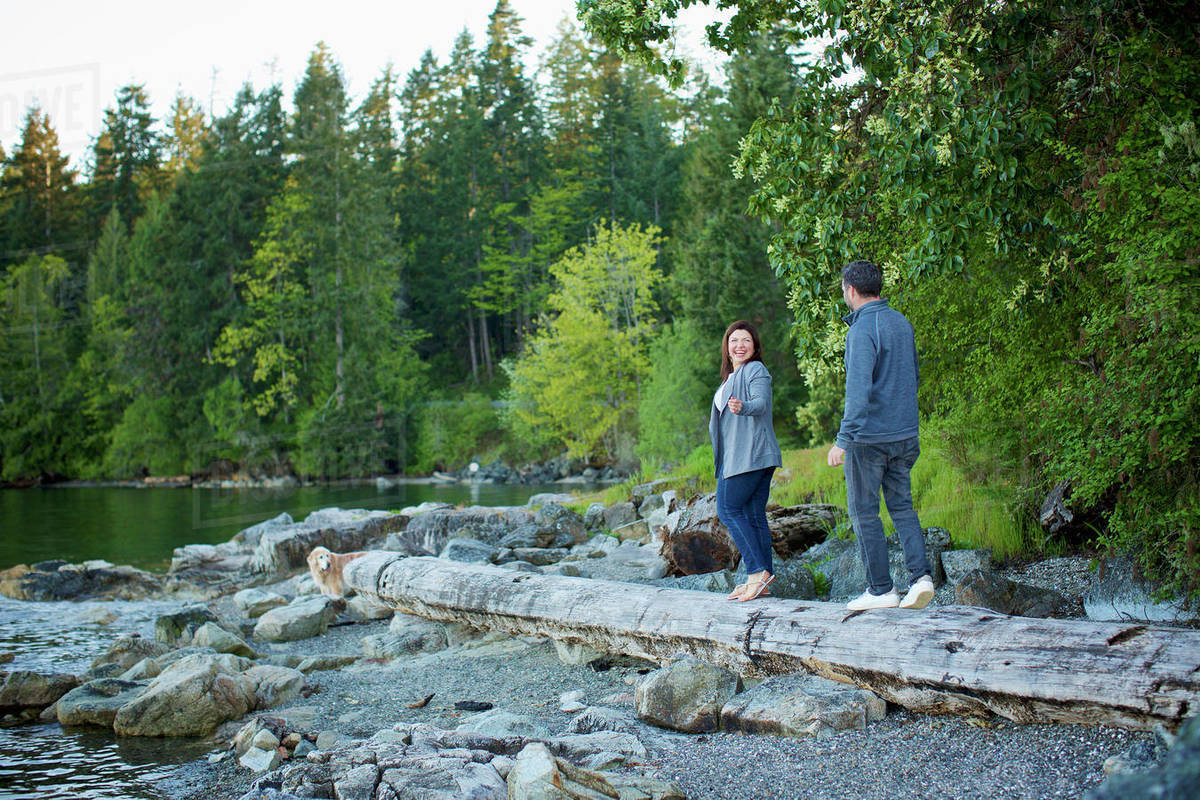 Happy couple walking on fallen log at lakeside in woods, Mill Bay, British Columbia, Canada Royalty-free stock photo