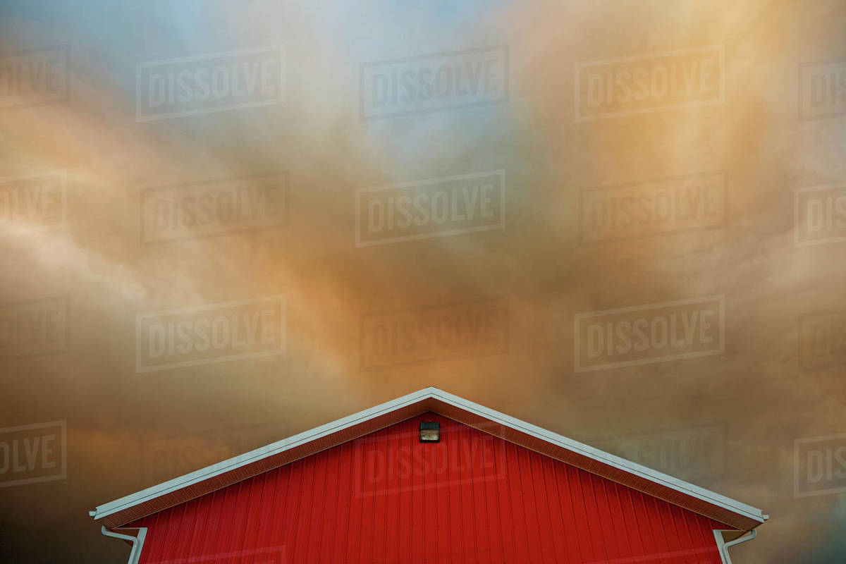 Orange clouds forming in dramatic sky over vibrant red barn Royalty-free stock photo
