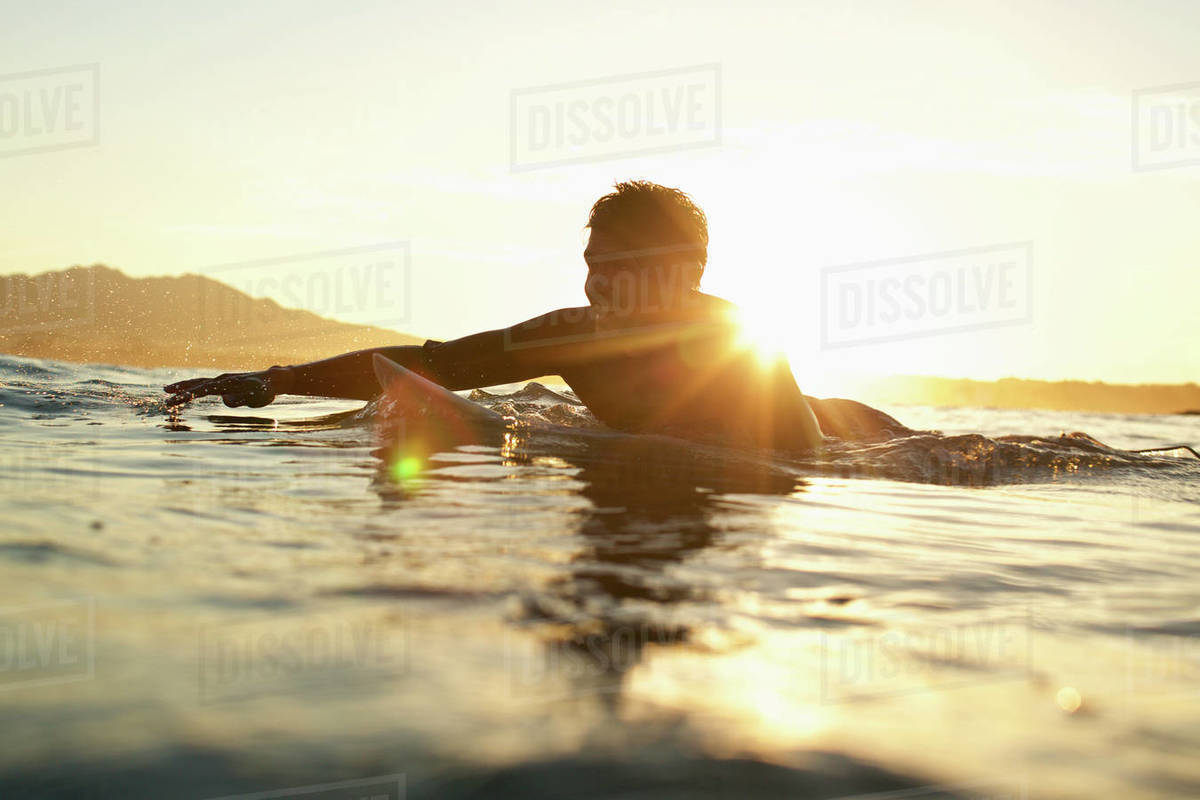 Happy male surfer paddling out on sunny, sunset ocean Royalty-free stock photo
