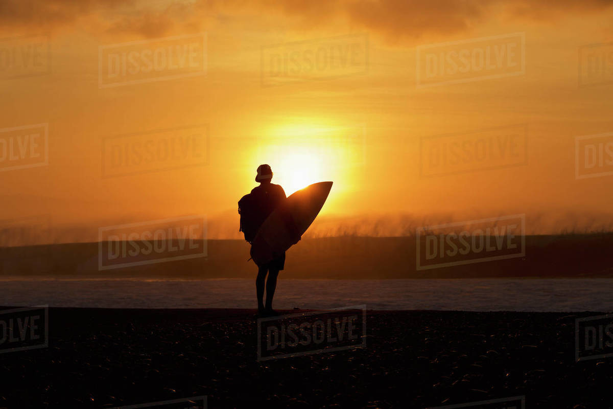 Silhouetted male surfer watching ocean wave from sunset beach Royalty-free stock photo