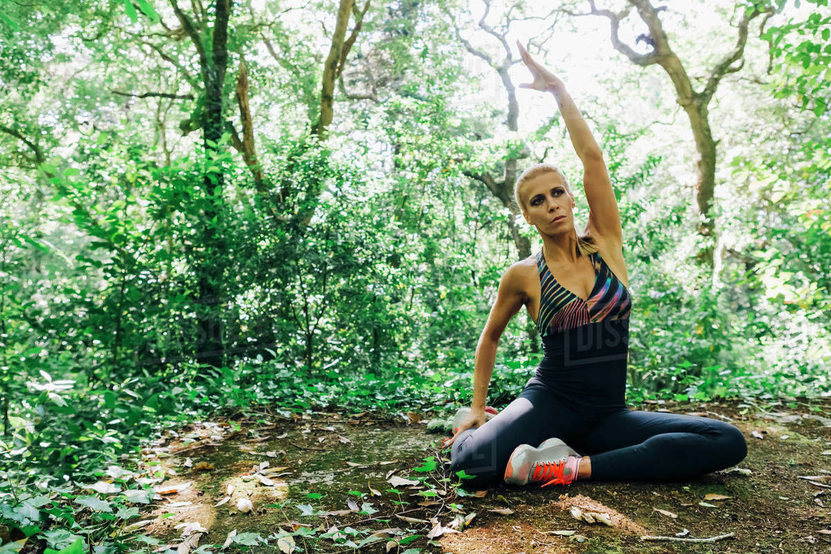Fit female personal trainer stretching in forest Royalty-free stock photo