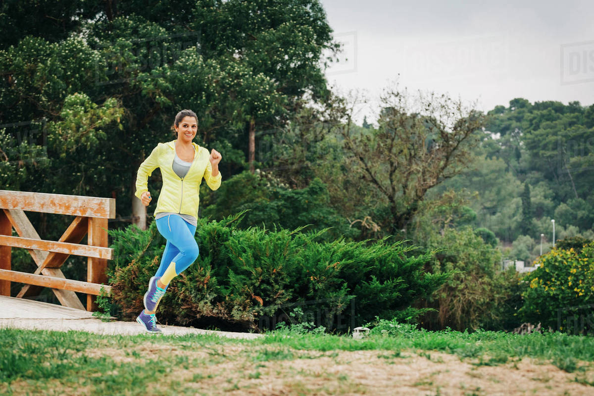 Portrait fit female personal trainer running in park Royalty-free stock photo