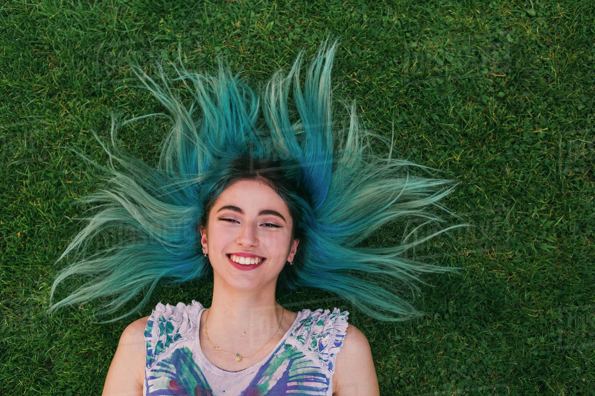 Overhead portrait carefree young woman with blue hair laying in grass Royalty-free stock photo