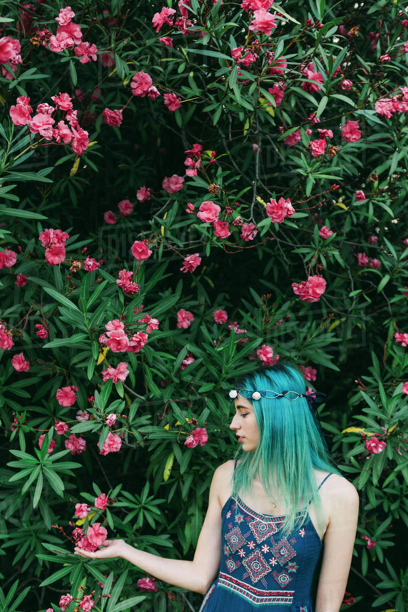 Serene young woman with blue hair standing below flowering tree Royalty-free stock photo