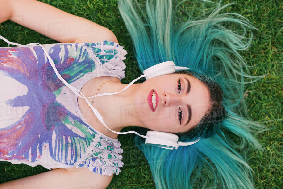 Overhead portrait young woman with blue hair listening to music with headphones Royalty-free stock photo