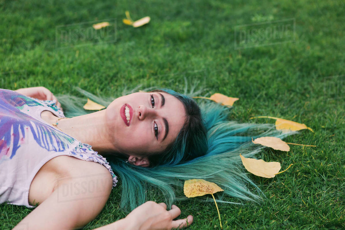 Portrait serene young woman with blue hair laying in grass with autumn leaves Royalty-free stock photo