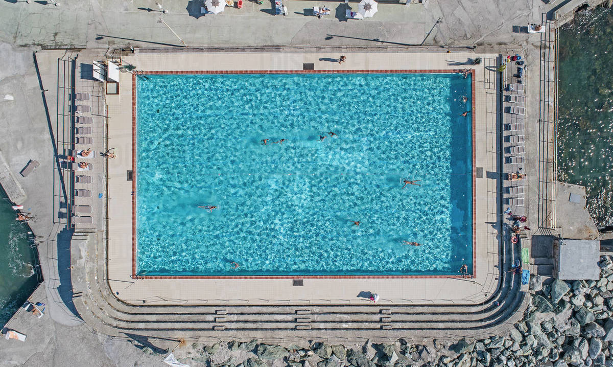 Aerial view from above tourists swimming in sunny, blue resort swimming pool, Genoa, Liguria, Italy Royalty-free stock photo