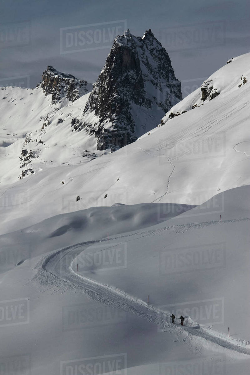 Snowshoers on sunny, snowy mountain slope, Vals, Canton of Grisons, Switzerland Royalty-free stock photo