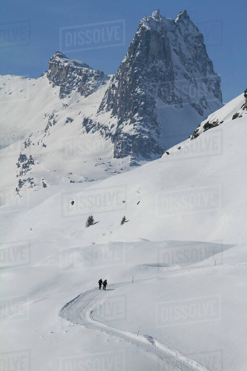 People snowshoeing on sunny, snow covered mountain, Vals, Canton of Grisons, Switzerland Royalty-free stock photo