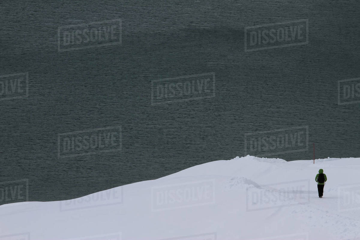 Snowshoer on snowy slope overlooking lake Royalty-free stock photo