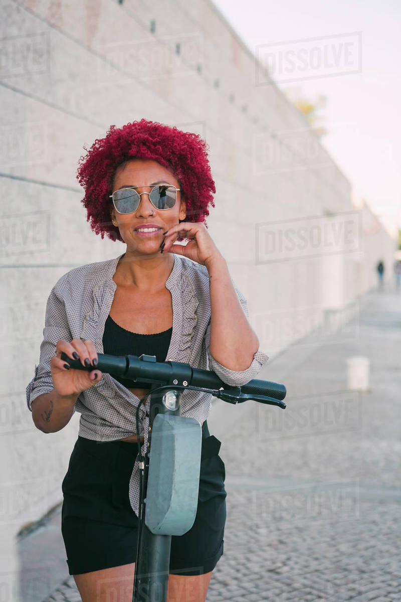 Portrait confident woman using shared public electric push scooter Royalty-free stock photo