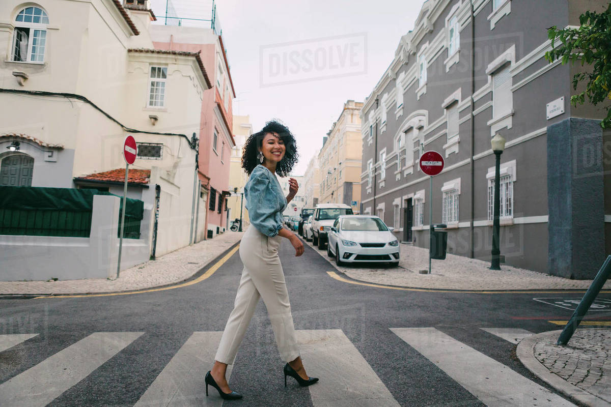 Portrait happy, stylish woman crossing city street Royalty-free stock photo