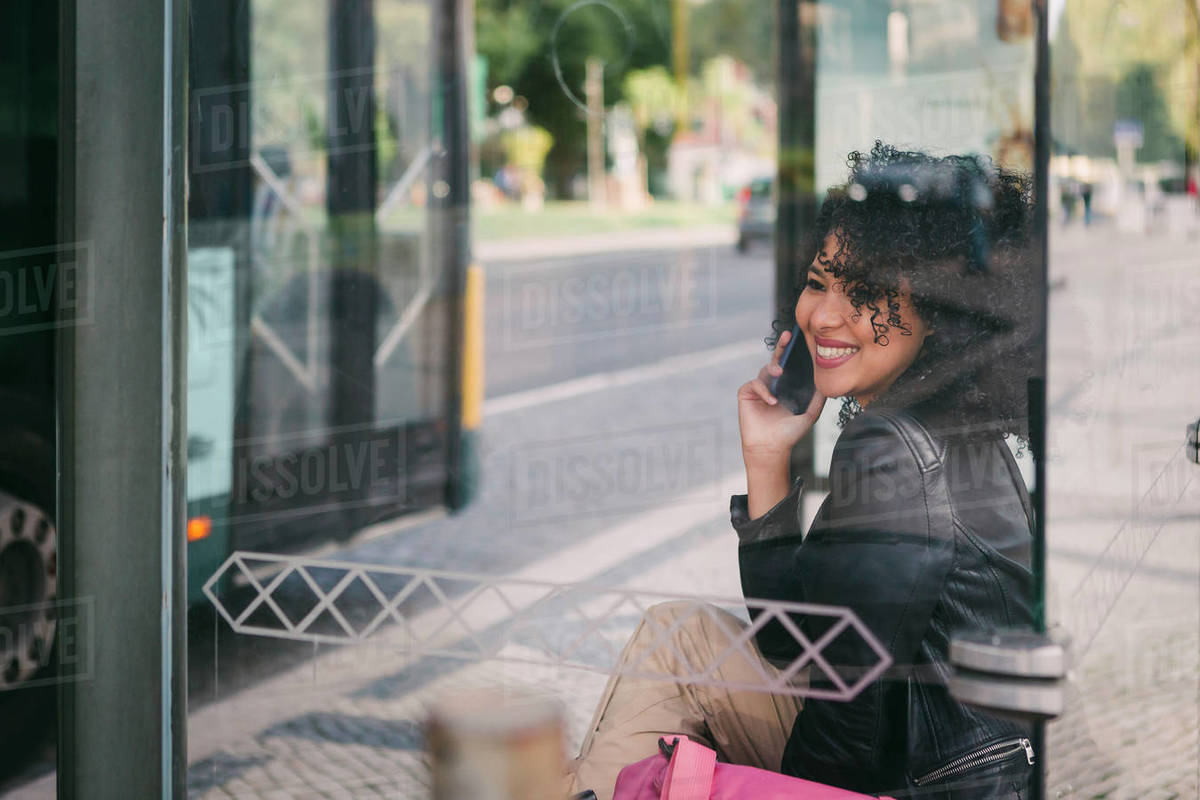 Happy young woman talking on smart phone at bus stop Royalty-free stock photo