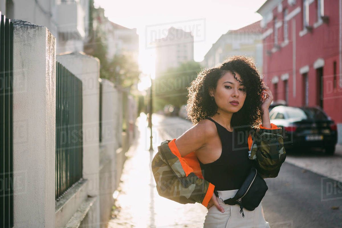 Portrait confident, stylish young woman on sunny city street Royalty-free stock photo