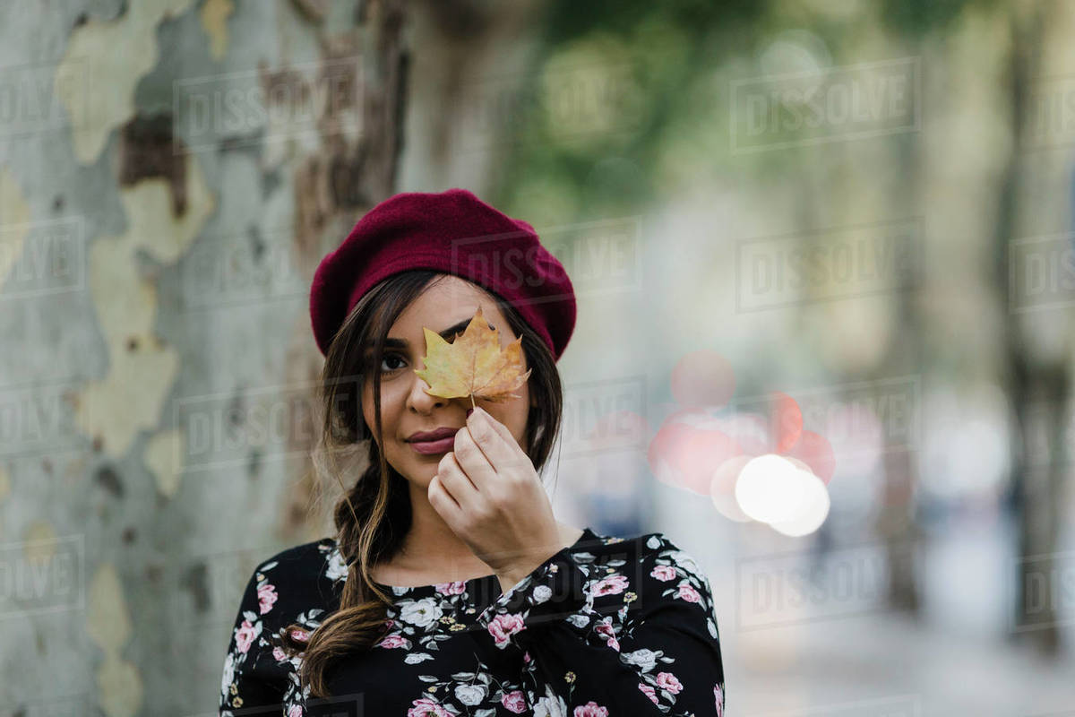 Portrait young woman in beret holding autumn leaf in park Royalty-free stock photo