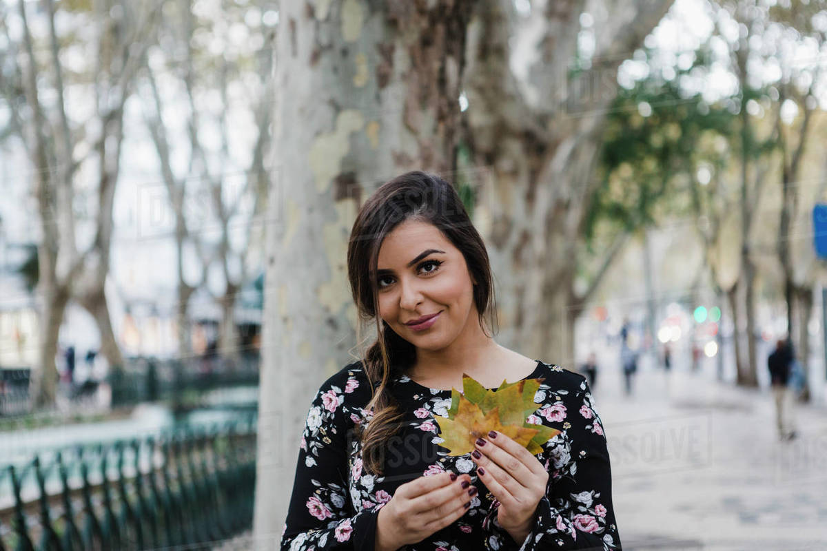Portrait smiling young woman holding autumn leaves in urban park Royalty-free stock photo