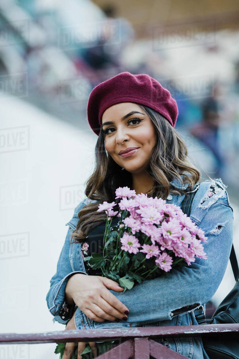 Portrait smiling young woman in beret holding flower bouquet Royalty-free stock photo