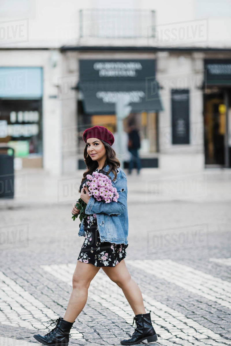 Portrait confident young woman crossing city street with bouquet of flowers Royalty-free stock photo