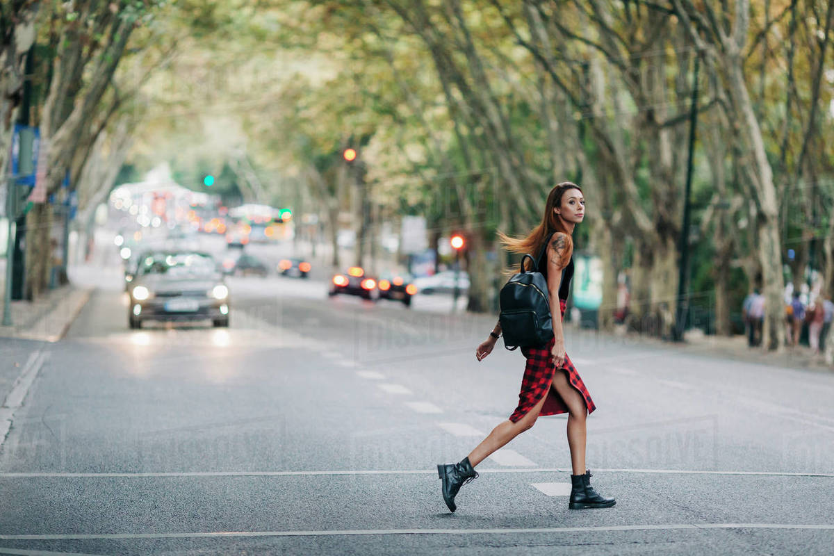 Young woman crossing city street Royalty-free stock photo