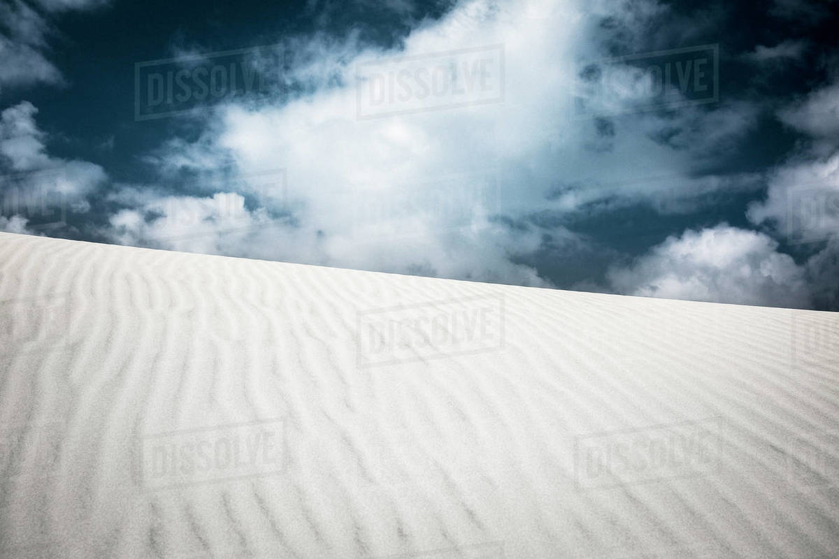 Pattern over sand dune below clouds in sky Royalty-free stock photo