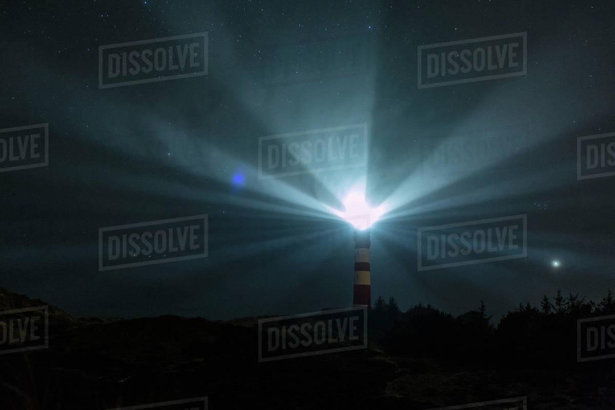 Light beacons illuminating from lighthouse under starry night sky, Wittduen, Germany Royalty-free stock photo