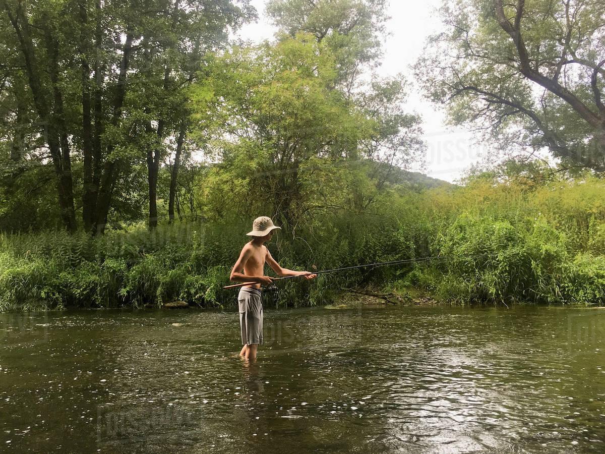Boy fishing in rural river Royalty-free stock photo