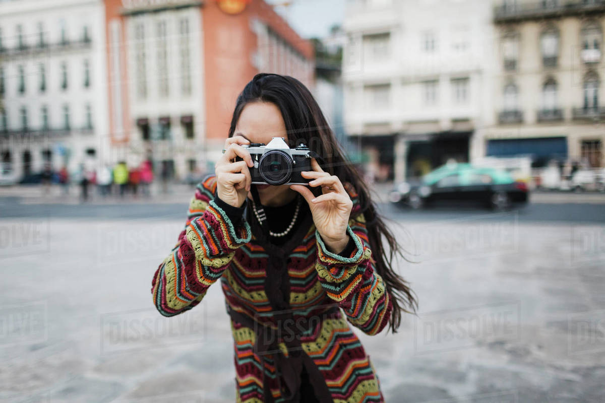 Portrait female tourist using camera on city street Royalty-free stock photo