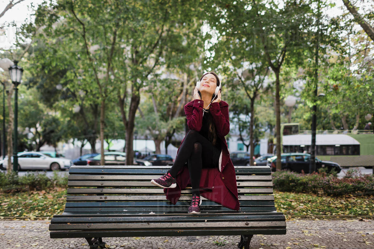 Carefree woman listening to music with headphones on urban park bench Royalty-free stock photo