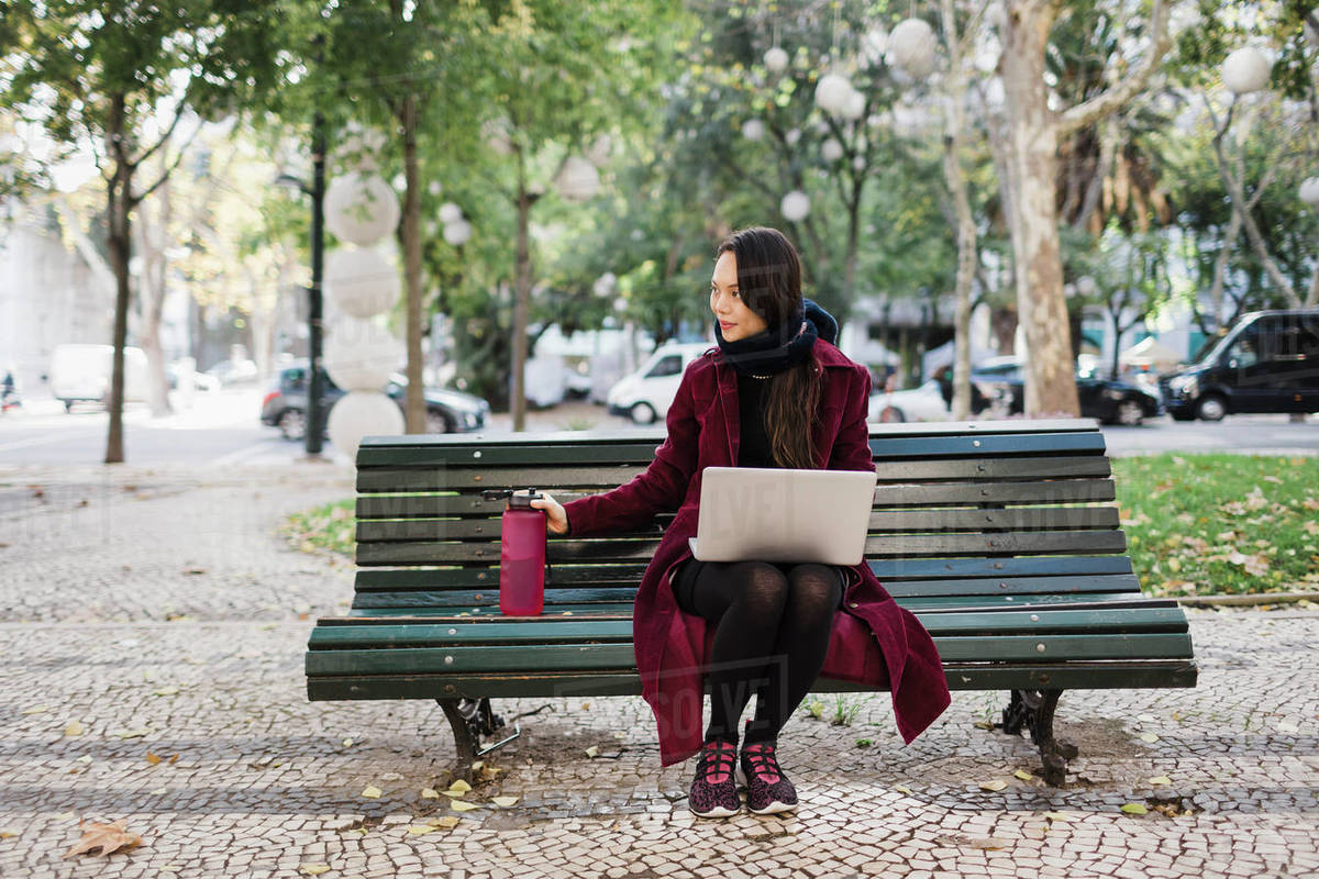 Woman with water bottle working at laptop in autumn city park Royalty-free stock photo