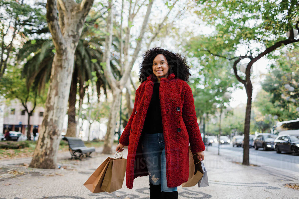 Portrait carefree young woman with shopping bags on urban sidewalk Royalty-free stock photo