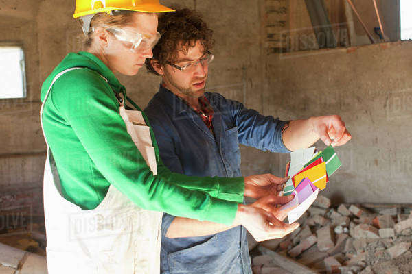 Two manual workers reviewing color samples on a building site Royalty-free stock photo