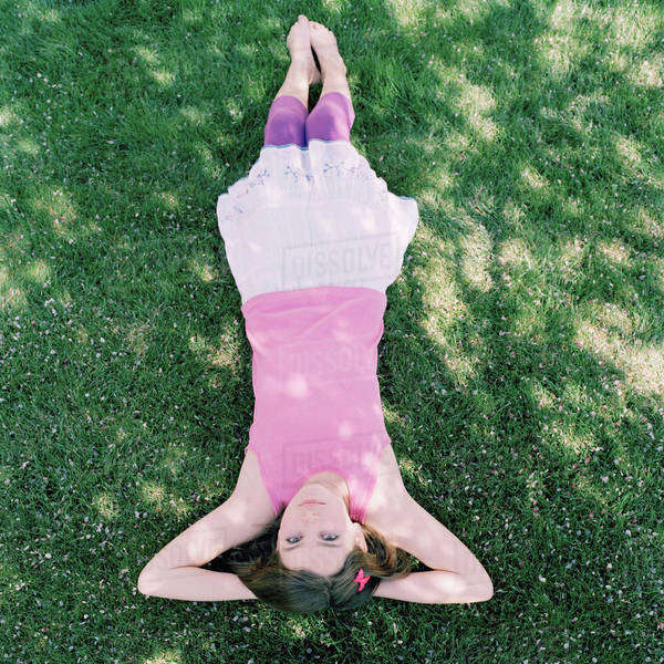 A girl lying in grass with hands behind head, upside down view Royalty-free stock photo