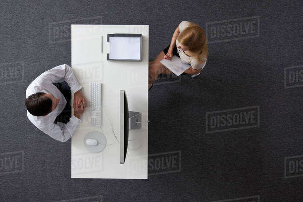 A businessman and businesswoman sitting across a desk from each other, overhead view Royalty-free stock photo