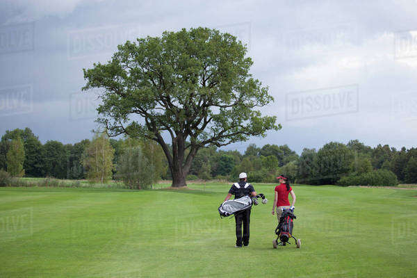 A female and male golfer walking with their golf bags, rear view Royalty-free stock photo