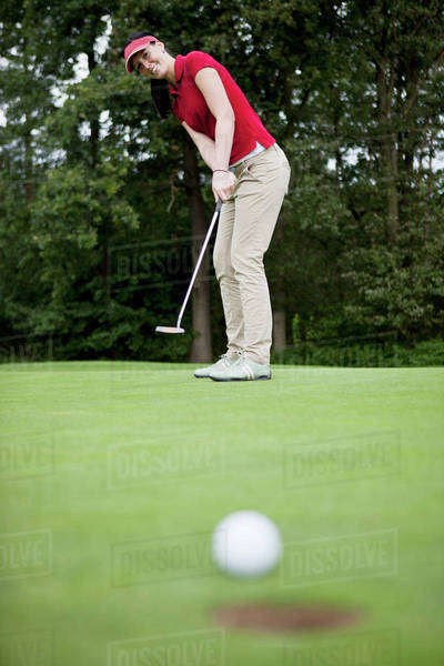 A female golfer putting, golf ball at edge of hole Royalty-free stock photo